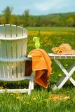 Présidence d'Adirondack dans l'herbe prête pour la détente Image stock