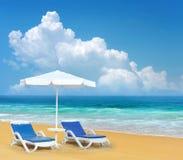 Présidence et parapluie de plage sur la plage de sable photos stock