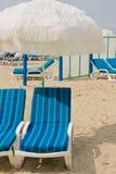 Présidences bleues à la plage avec le parapluie Photo stock