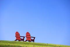 Présidences de pelouse rouges sur l'herbe Image stock