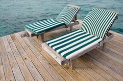 Présidences de plage sur le dock Images stock