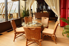 Présidences en osier et table dans le restaurant Photographie stock