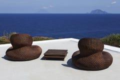 Présidences en osier sur la terrasse de bord de la mer Photographie stock