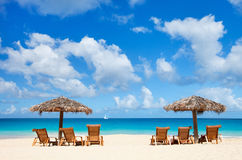 Présidences et parapluies sur la plage tropicale Image stock