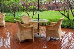 Présidences et table de rotin de patio en pleuvant Photographie stock