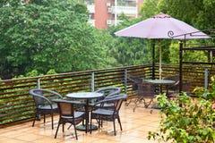 Présidences et table de rotin de patio en pleuvant Image stock