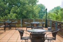 Présidences et table de rotin de patio en pleuvant Photographie stock libre de droits