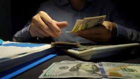 préstamo e hipoteca El hombre cuenta el dinero en la oficina almacen de metraje de vídeo