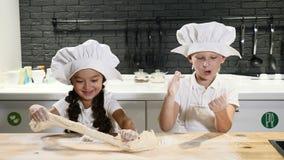 Prétention des adultes Deux enfants dans des chapeaux et des tabliers de chef jouent avec le dought le roulant et touchant Cuisso clips vidéos