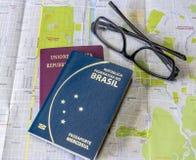Prévoyant les passeports brésiliens et italiens d'un voyage - sur la ville tracez avec des verres photographie stock