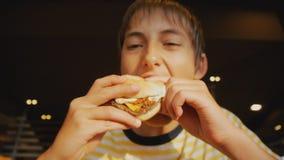Prêt-à-manger de consommation d'adolescent Tir en gros plan de cheeseburger acéré de garçon de l'adolescence dans le restaurant d banque de vidéos
