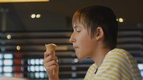 Prêt-à-manger de consommation d'adolescent Tir en gros plan de garçon de l'adolescence mangeant le cornet de crème glacée dans le clips vidéos