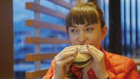 Prêt-à-manger de consommation de femme Portrait de jeune cheeseburger acéré et de mastication femelle caucasien dans le restauran banque de vidéos