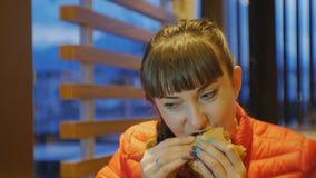 Prêt-à-manger de consommation de femme Tir en gros plan de cheeseburger acéré et de mastication femelle attrayant dans le restaur clips vidéos