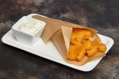 Prêt-à-manger L'homme de fromage figure du plat blanc, fond bleu Images stock