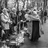 Prêtre bénissant les personnes heureuses pendant le cerem saint de dimanche de Pâques Photographie stock