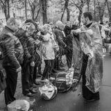 Prêtre bénissant les personnes heureuses pendant le cerem saint de dimanche de Pâques Photo libre de droits