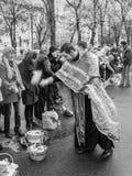 Prêtre bénissant les personnes heureuses pendant le cerem saint de dimanche de Pâques Image libre de droits