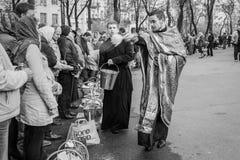 Prêtre bénissant les personnes heureuses pendant le cerem saint de dimanche de Pâques Image stock