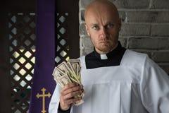 Prêtre catholique avec l'argent dans sa main images libres de droits
