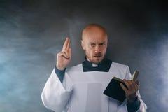 Prêtre catholique dans le surplis blanc et chemise noire avec la bible de lecture de collier d'ecclésiastique photo stock