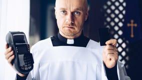Prêtre catholique tenant le lecteur de carte de crédit images libres de droits