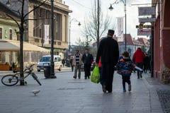 Prêtre habillé la marche noire, en tenant une main de childs et en portant un sac avec des épiceries photos stock