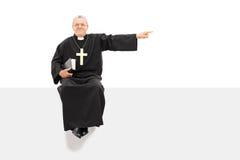 Prêtre mûr se dirigeant avec sa main posée sur le panneau Image libre de droits