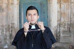 Prêtre menotté regardant très bouleversé photos libres de droits