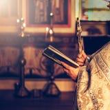 Prêtre priant dans l'église tenant la bible et la croix de houx image libre de droits