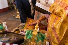 Prêtre tenant le ` s de jeune mariée et les mains du ` s de marié pendant la cérémonie de mariage images libres de droits
