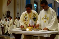 Prêtres catholiques prenant la communion pendant la masse de congrégation photographie stock libre de droits