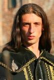 Príncipe medieval joven con el sable y la capa negra Foto de archivo
