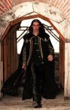 Príncipe medieval joven con el sable y la capa negra Imagenes de archivo