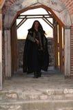 Príncipe medieval joven con el sable y la capa negra fotografía de archivo