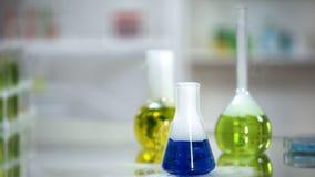 Próbka błękitna substancja w kolbiastej pozycji na stole laboratorium, płuczkowy agent zdjęcie stock