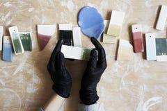 Próbki barwiona emalia dla koloru ceramicznego w rękach, pracuje proces w studiu, glina, drewno, craftÑŽ Fotografia Stock