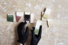 Próbki barwiona emalia dla koloru ceramicznego w rękach, pracuje proces w studiu, glina, drewno, rzemiosło Obrazy Stock