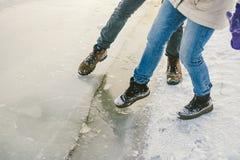 Próbujący niebezpieczeństwo stopa, bada cienkiego lód blisko brzeg Para kochankowie chodzi z spacerem wzdłuż zamarzniętego jezior obrazy stock