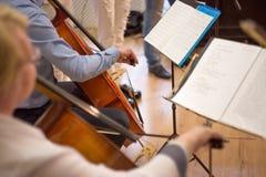 próximo acima de um homem e de uma mulher que jogam o violoncelo, um concerto real imagem de stock royalty free
