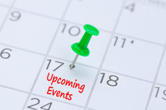 Próximos eventos escritos em um calendário com um pino verde do impulso a r foto de stock