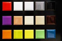 Prövkopior av keramiska tegelplattor av olika färger på en svart bakgrund royaltyfri foto