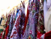 Prövkopior av ljusa kvinnors scarves hänger på ett rep i rad fotografering för bildbyråer