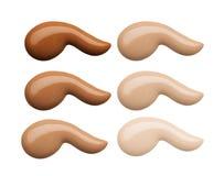 Prövkopior för fundamentframsidamakeup Uppsättning av kosmetiskt vätskefundament eller kräm i olika slaglängder för färgfläcksudd royaltyfri bild