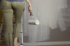 prövkopior för målarfärgrulle Härlig kvinnamålningvägg med målarfärgrolle Arkivfoton