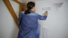 prövkopior för målarfärgrulle Härlig kvinnamålningvägg med målarfärgrullen stock video