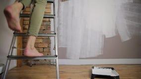 prövkopior för målarfärgrulle Härlig kvinnamålningvägg med målarfärgrullen arkivfilmer