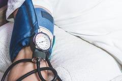 Prüfen Sie mit einem Blutdruckmessgerät stockfoto