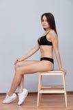 Prüfen Sie Schüsse das vorbildliche Aufstellungsc$sitzen jungen Brunette auf Leiter gegen Wand auf Schnappschussportfolio der mod lizenzfreies stockfoto