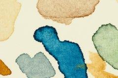 Prüfen Sie vibrierende Farbenstellen des Aquarells auf starkem Aquarellpapierblatt, verließ als Gruppe kleine Tropfen und spritzt Stockfoto